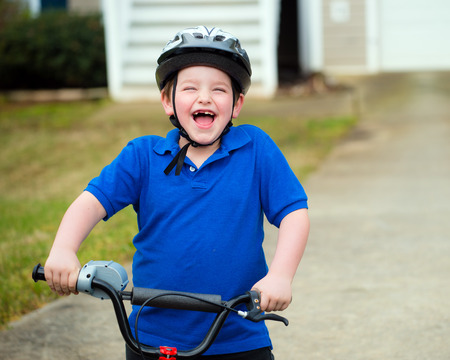 Happy child riding his bike outside his home photo