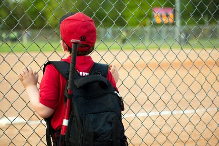 Young baseball player watching game from outside fence Stock Photo
