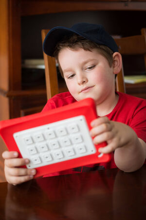 Child using tablet computer while sitting at dining room table 版權商用圖片
