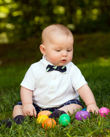 red haired: Cute infant baby boy playing with Easter eggs