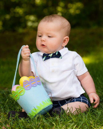 Cute infant baby boy playing with Easter eggs and basket 版權商用圖片