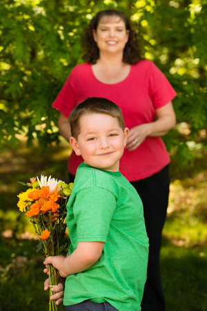 Little boy giving flowers to his mom on mother