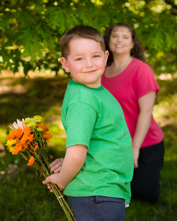 Little boy giving flowers to his mom on mother photo