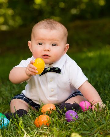 Cute infant baby boy playing with Easter eggs photo