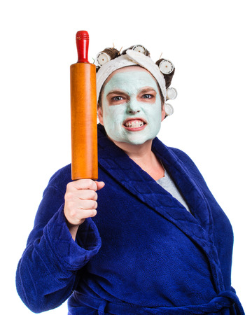 hair roller: Mean and ugly housewife with facial mask, hair rollers and rolling pin isolated on white