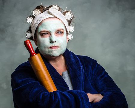 Media e brutta casalinga con maschera facciale, bigodini e mattarello