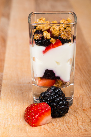 Mini mixed berry yogurt parfait in dessert shot glass or trifle with strawberries and blackberries