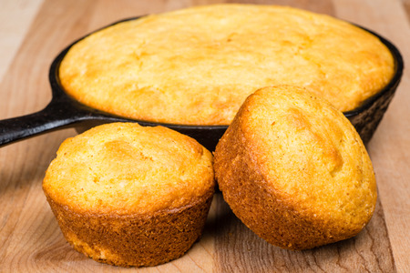 cast: Cornbread muffins and cornbread pone in an iron skillet Stock Photo