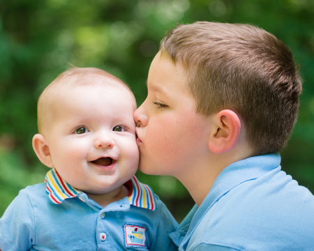 Happy baby boy kissed by his older brother photo