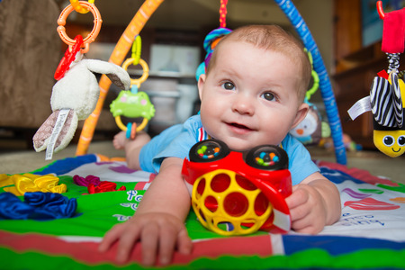 Happy and curious infant baby boy playing on activity mat photo
