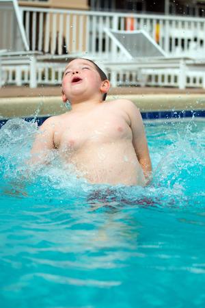 Young boy splashing into pool while swimming 版權商用圖片
