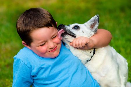 dog days: Niño feliz que se pasó la lengua por su perro mascota