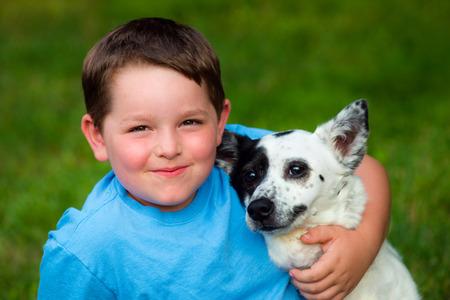 Kind liefdevol omhelst zijn hond Stockfoto - 29044153