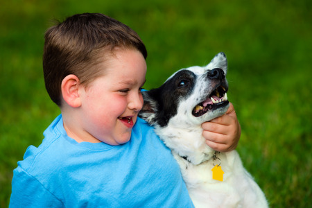 Child lovingly embraces his pet dog 版權商用圖片 - 29044173