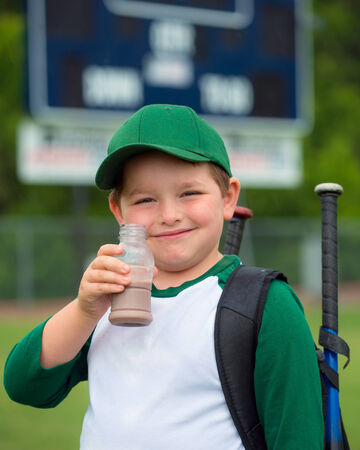 Child baseball player drinking chocolate milk after game photo