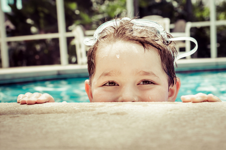 Young child peeking out of pool while swimming in vintage filtered image