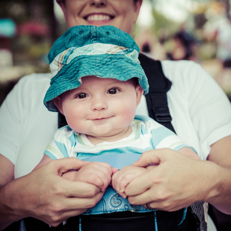 baby carrier: Baby boy riding in infant carrier by mother outdoors at crowded park in vintage filtered image Stock Photo