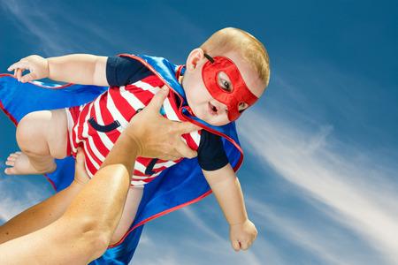 Boldog kisfiú viselt szuperhős jelmezben repül az égen Stock fotó