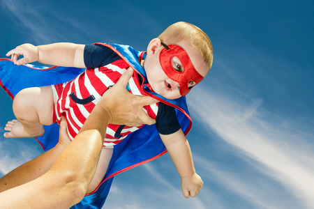 Happy baby boy wearing superhero costume flying in the sky photo