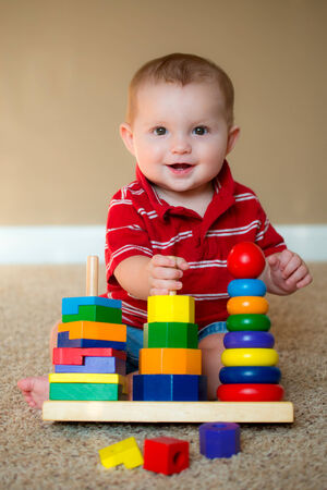 expertise concept: Baby boy playing with stacking learning toy