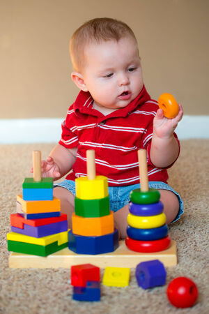 Baby boy playing with stacking learning toy 版權商用圖片 - 30116933