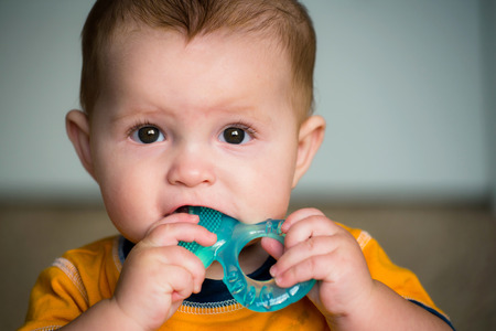 biting: Baby chewing on teething ring toy