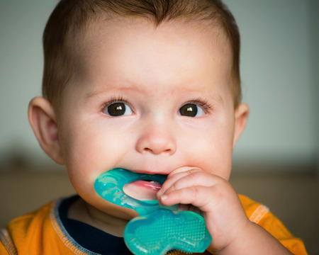 teething: Baby chewing on teething ring toy