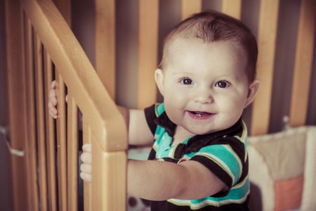 Happy baby standing up in his crib in image with vintage filter 版權商用圖片