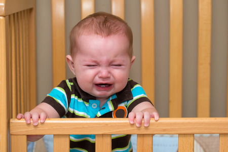 Crying unhappy baby standing in his crib photo