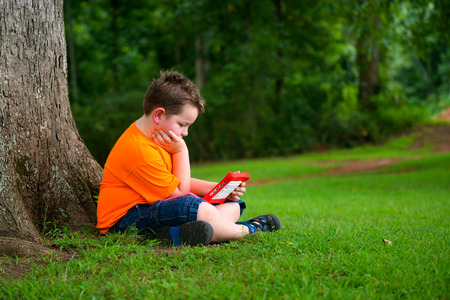 Young boy using tablet outdoors at park photo