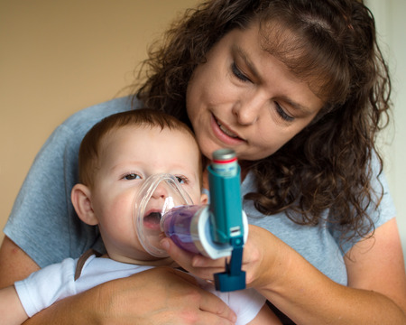 Infant getting breathing treatment from mother while suffering from illness photo