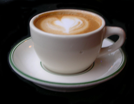 cappaccino: Latte in coffee cup with heart design on black background. Stock Photo