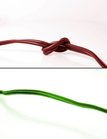 scenarios: Conceptual photo showing two scenarios: problem and fixed problem. On top is red cable with knot - indicating problems. On bottom is green cable indicating problem free communication.