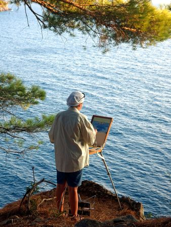 Woman is standing on the cliff, above the sea, and paints.  Stock Photo