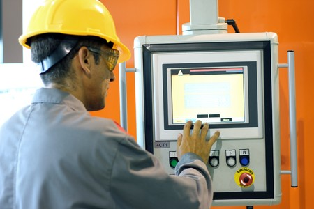 control panel: Male technician using industrial control panel of the PET blow molding machine.