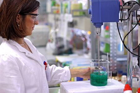 mixing: A young chemical engineer  working at the chemistry laboratory.