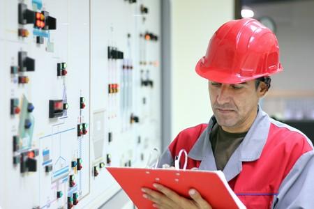 monitoreo: Ingeniero de pie delante del panel de control en la sala de control y los resultados de las mediciones de la escritura.  Foto de archivo