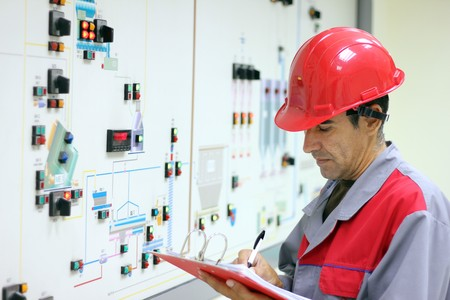 tablero de control: Ingeniero de pie delante del panel de control en la sala de control y los resultados de las mediciones de la escritura.  Foto de archivo