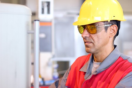 Portrait of a worker wearing protective helmet and safety glasses.