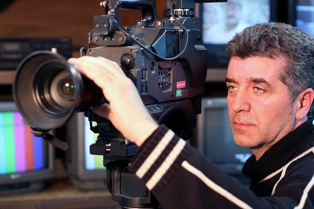 Camera operator using a television camera. photo