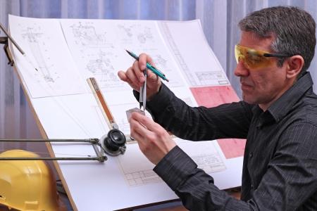 dibujo tecnico: Ingeniero mec�nico analizar su dise�o. Medici�n de las dimensiones del modelo de metal con una pinza divisor.