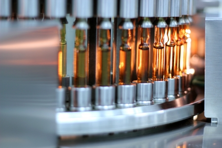 pharmaceutical plant: Inspects vials and ampoules for particulates in liquid and container defects.