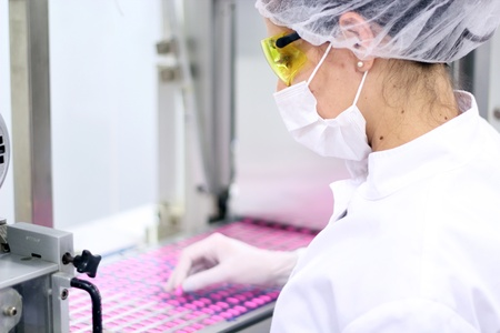 Technician inspecting the quality of pills at a pharmaceutical plant. Stock Photo
