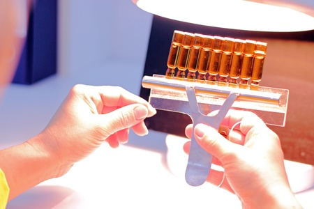 Technician inspects vials and ampoules for particulates in liquid and container defects. Stock Photo