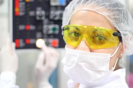 manufactura: Un t�cnico femenino est� supervisando el proceso de embalaje de la p�ldora. Foto de archivo