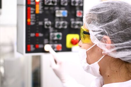 plant drug: A female technician is monitoring the process of pill packaging.