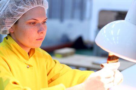 particulates: Technician inspects vials and ampoules for particulates in liquid and container defects. Stock Photo