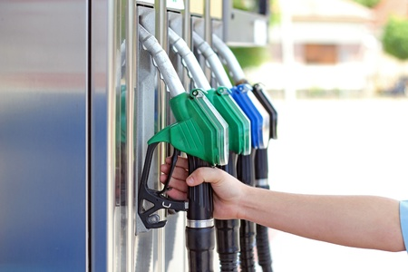Close-up of a mens hand using a fuel nozzle at a gas station.