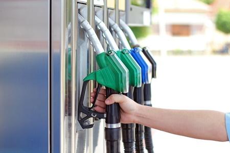 l p g: Primer plano de la mano de los hombres mediante un inyector de combustible en una gasolinera.