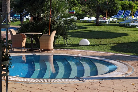 Man cleaning the luxury swimming pool.